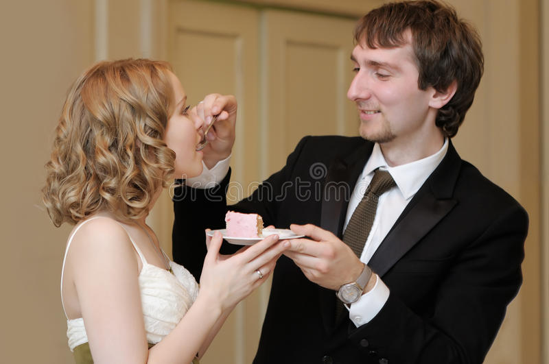 Bride and groom eating wedding cake stock photo