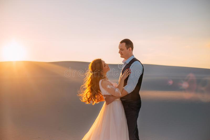 The bride and groom embrace in the warm sunshine at sunset. Beautiful brunette girl with long hair looks at a tall man stock photography