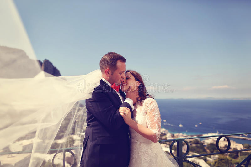 Bride and groom embracing with beautiful sea scape in background. Capture of Bride and groom embracing with beautiful sea scape in background stock photo