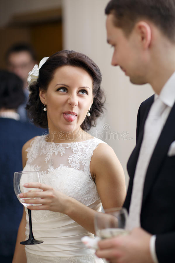 Bride and groom enjoy a drink at the wedding. Bride and groom enjoy a quiet moment together and a drink of white wine at their wedding reception stock images