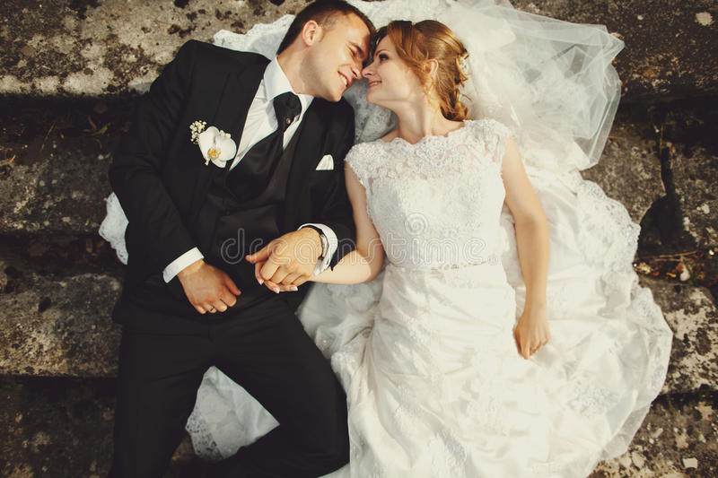 Bride and groom enjoy the moment lying on the old stone footstep royalty free stock images