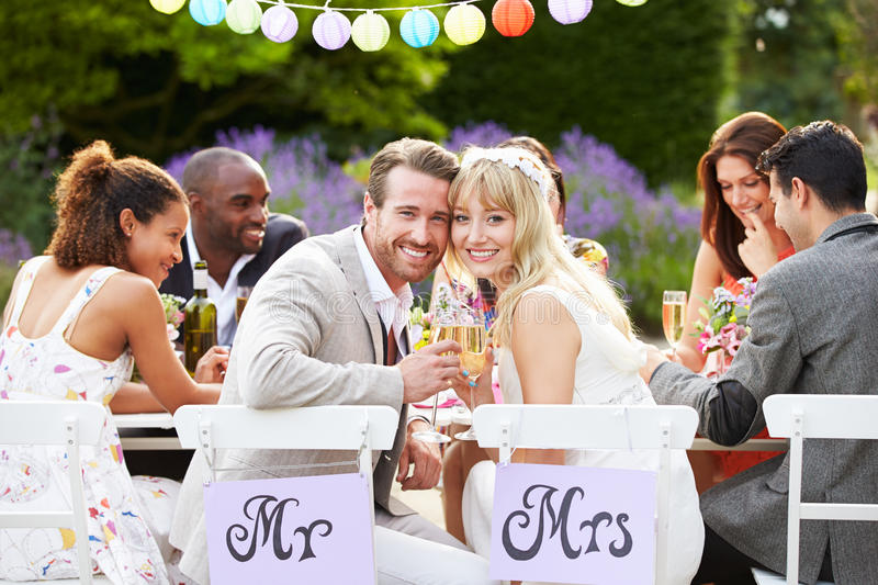 Bride And Groom Enjoying Meal At Wedding Reception. Looking To Camera Smiling stock photos