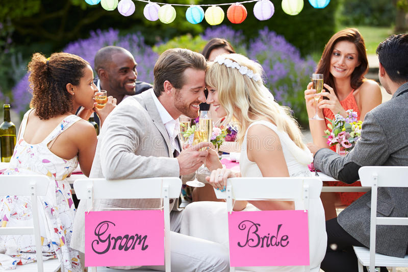 Bride And Groom Enjoying Meal At Wedding Reception royalty free stock images