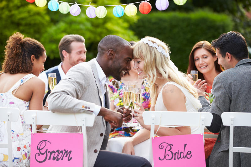 Bride And Groom Enjoying Meal At Wedding Reception. Smiling At Each Other With Heads Touching stock photo