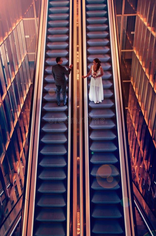 Bride and groom on escalators stock photography