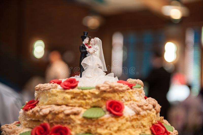 Bride and groom figures made of sugar on top of wedding cake. With blurred background stock photo