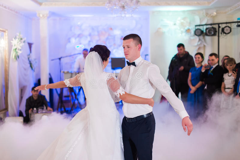 Bride and groom first wedding dance in white bright hall with blurred background stock image