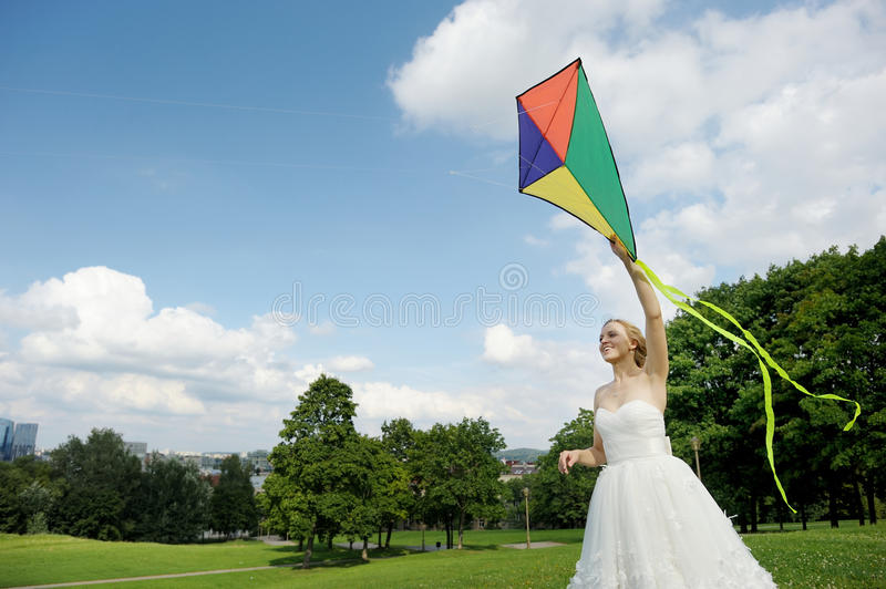 Bride and groom flying a kite on a wedding day stock images
