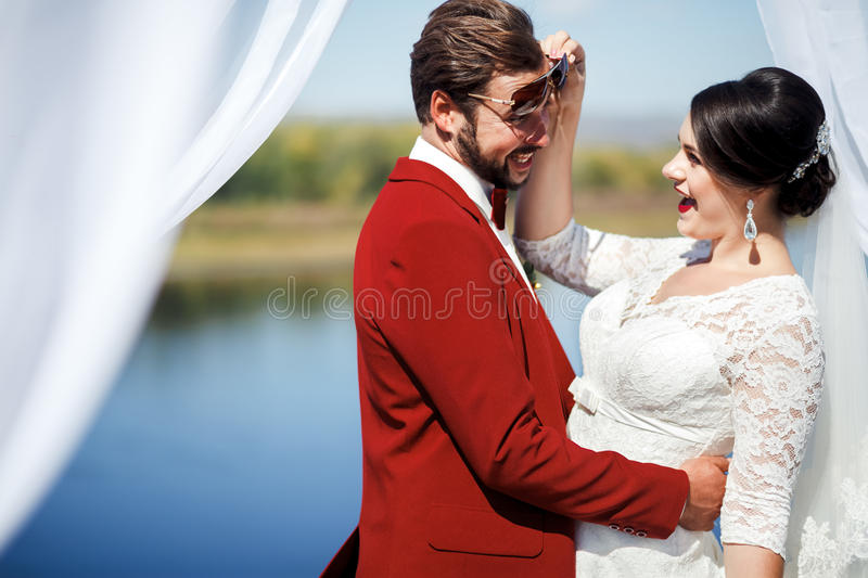 Bride and groom fooling around at photo shoot after ceremony, inside arch with white cloths fabric. Wedding Color. Bride and groom fooling around at a photo royalty free stock image
