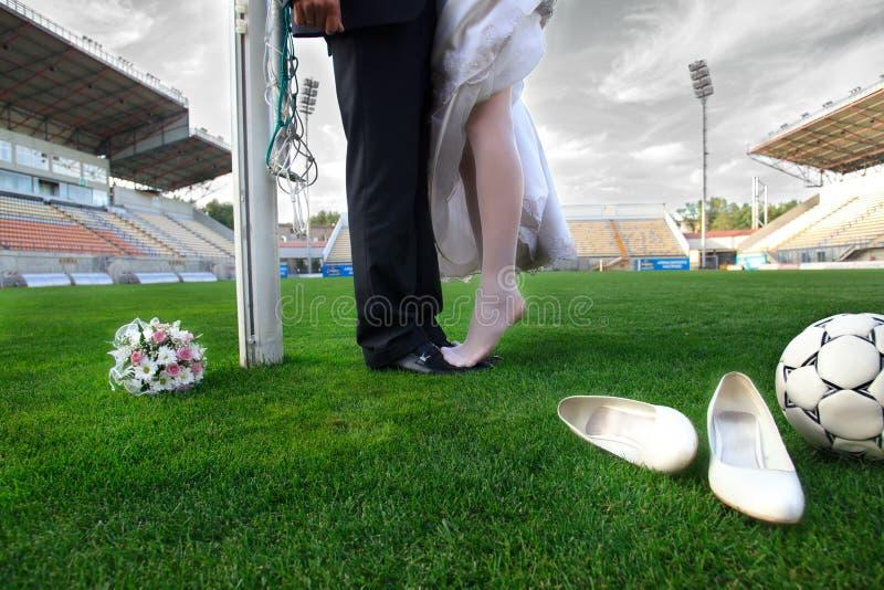 Bride and groom on football stadium stock photography