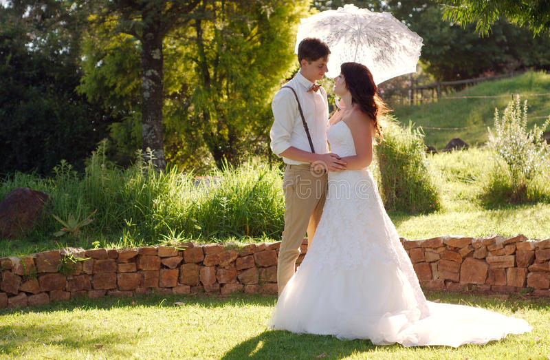 Bride and groom in garden wedding with parasol royalty free stock photos