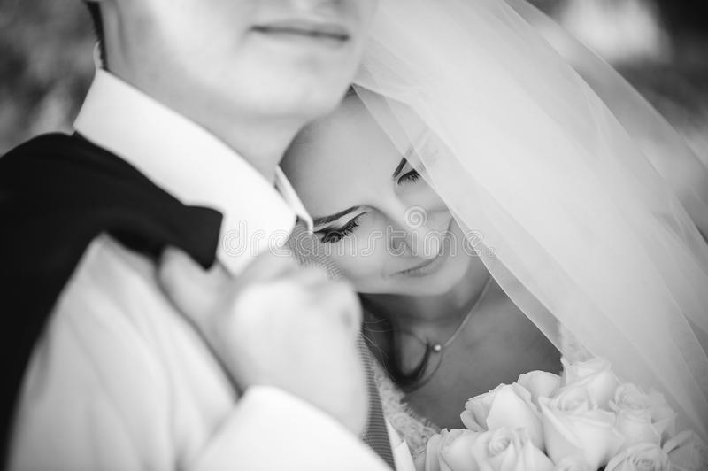 The bride with the groom gently laid her head on her shoulder, a white veil covers her face, a happy wedding couple, a contrast bl. Ack and white photograph royalty free stock photography