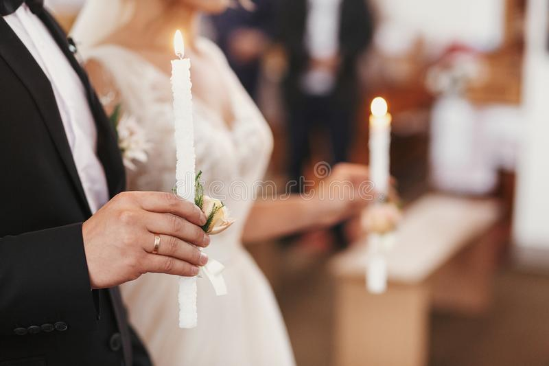 Bride and groom in golden crowns standing with candles in hands. During wedding ceremony. Spiritual couple. Wedding matrimony in church. Emotional romantic royalty free stock images