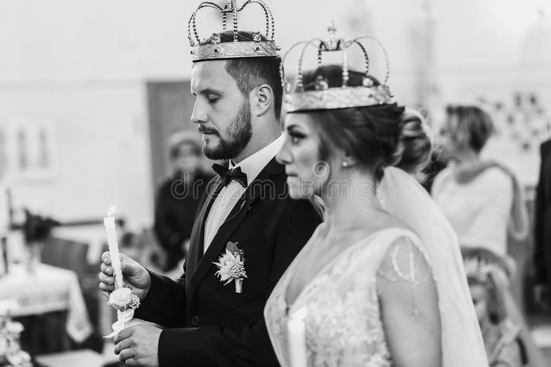 Bride and groom in golden crowns standing with candles in hands. During wedding ceremony. Spiritual couple. Wedding matrimony in church. Emotional romantic royalty free stock photos