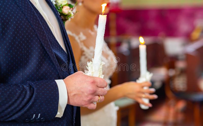 Bride and groom holding the candles. Close up. Bride and groom in golden crowns standing with candles in hands during wedding ceremony. Spiritual couple. Wedding royalty free stock photos