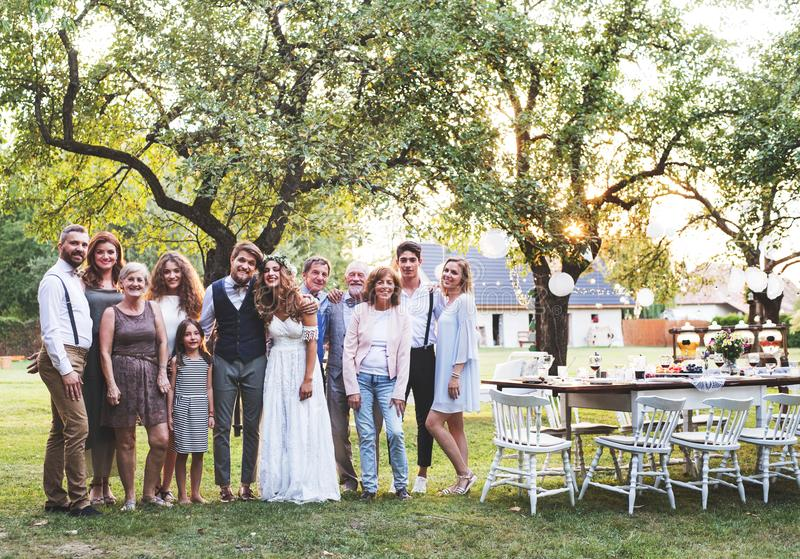 Bride, groom, guests posing for the photo at wedding reception outside in the backyard. royalty free stock photography