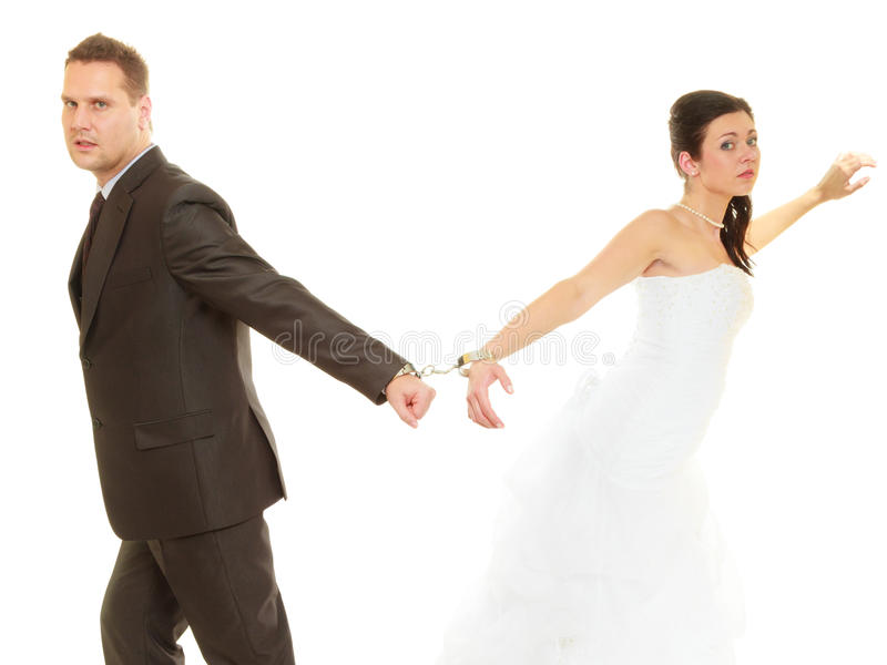 Bride and groom in handcuffs wearing wedding outfits royalty free stock photos