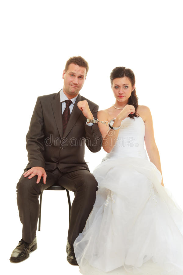 Bride and groom in handcuffs wearing wedding outfits stock image