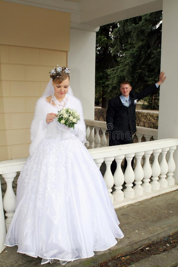 Bride and groom at handrail royalty free stock photography