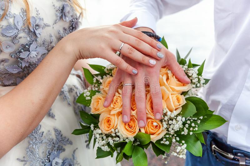 Bride and groom hands with wedding rings against background of bridal bouquet of flowers royalty free stock images