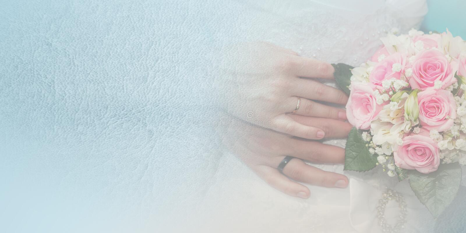 Bride and groom hands with wedding rings and bouquet of roses stock photos