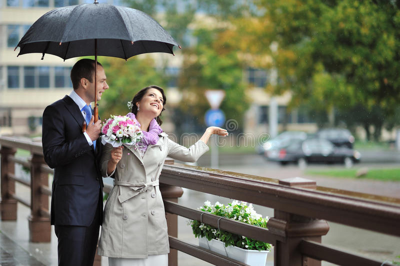 Download Bride And Groom Hiding From The Rain, While Catching Raindrops A Stock Photo - Image: 26830058