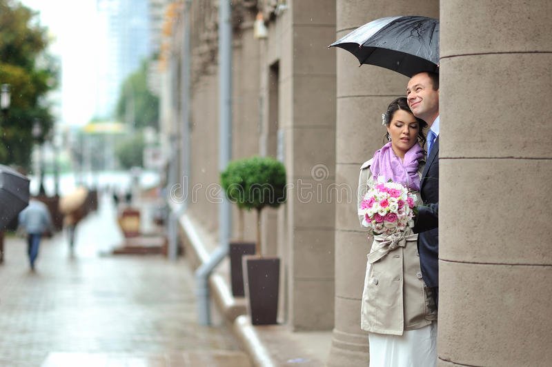 Bride And Groom Hiding From Rain In An Old Town Royalty Free Stock Photo