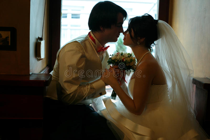 Bride and groom hold each other hands sitting in the cosy corner. Of a restaurant royalty free stock images