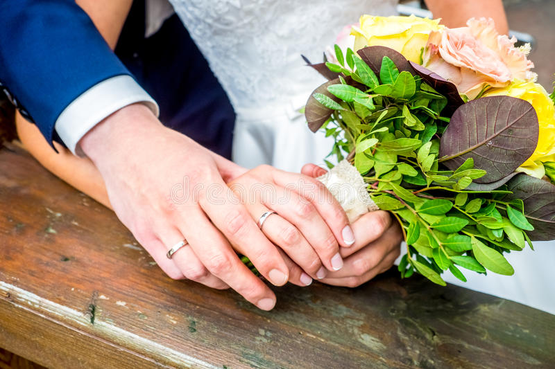 The bride and groom hold each other's hands stock photos