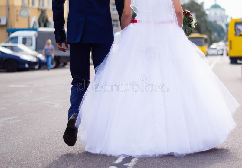 The bride and groom hold hands themselves while they walking on the road in city. Wedding in detail royalty free stock photography