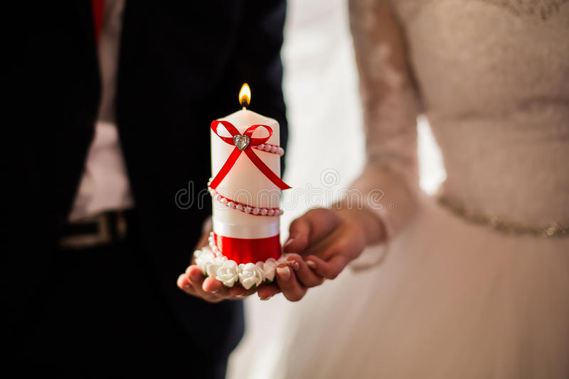 Bride and groom holding a beautiful decorative burning candle, male and female hand with wedding rings, stock photos