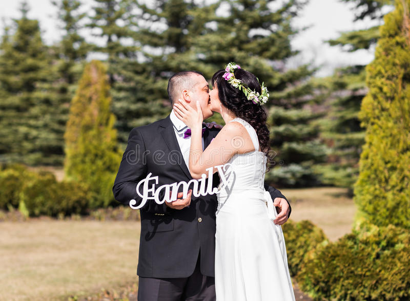 Bride and groom holding bouquet and wooden word family stock image