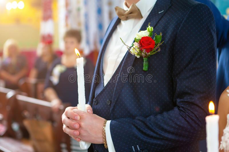 Bride and groom holding the candles. Close up. Bride and groom in golden crowns standing with candles in hands during wedding ceremony. Spiritual couple royalty free stock images