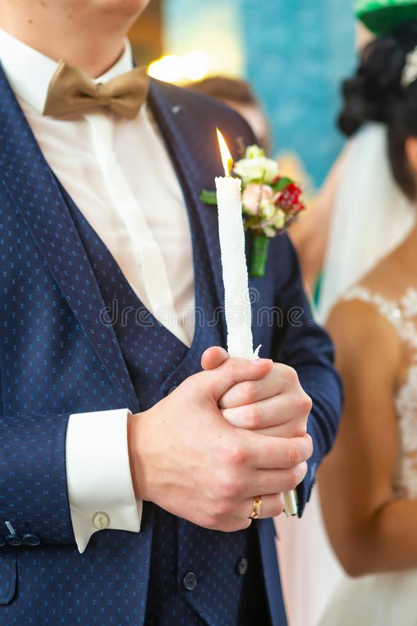Bride and groom holding the candles. Close up. Bride and groom in golden crowns standing with candles in hands during wedding ceremony. Spiritual couple stock photo