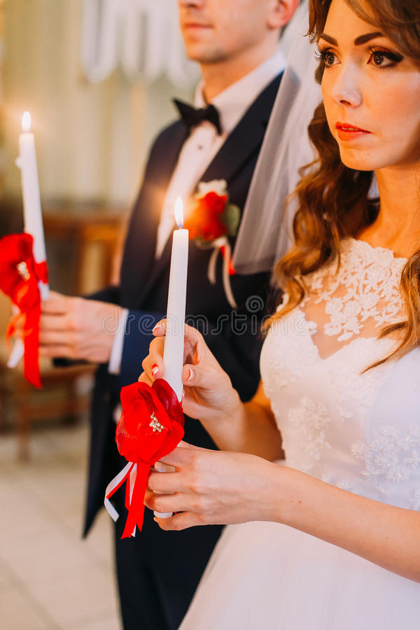 Bride and groom holding candles during the traditional wedding ceremony royalty free stock photos