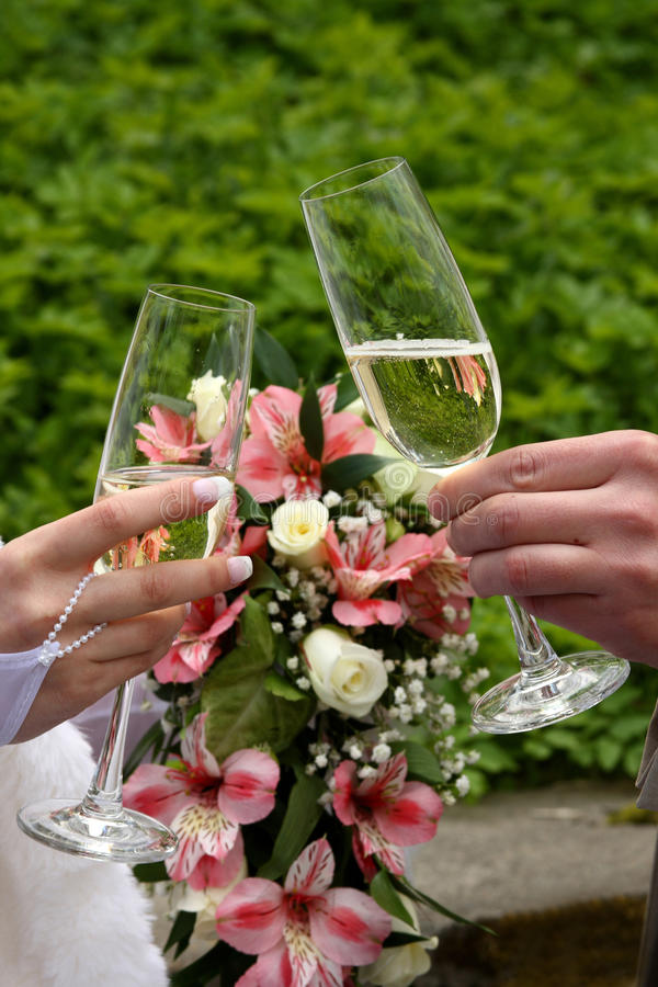 Bride and groom holding champagne glasses. Champagne Toast . Wedding glasses in their hands stock photo