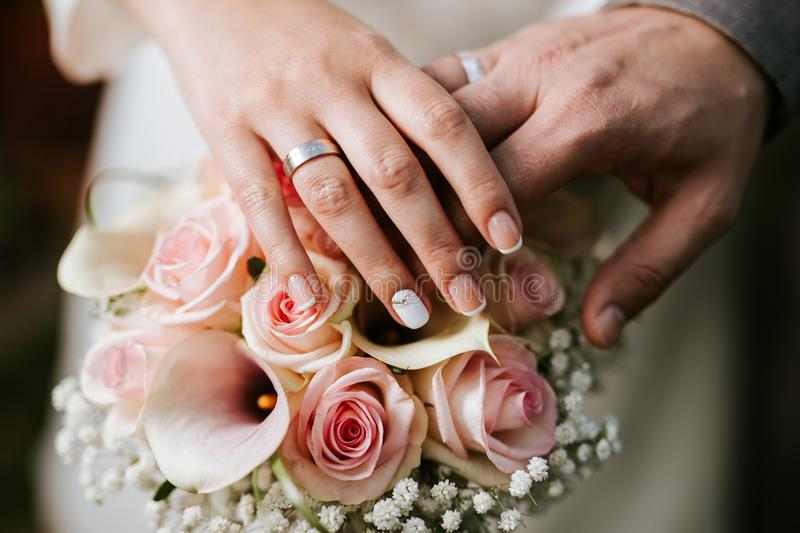 Bride and groom holding hand on the bouquet stock image