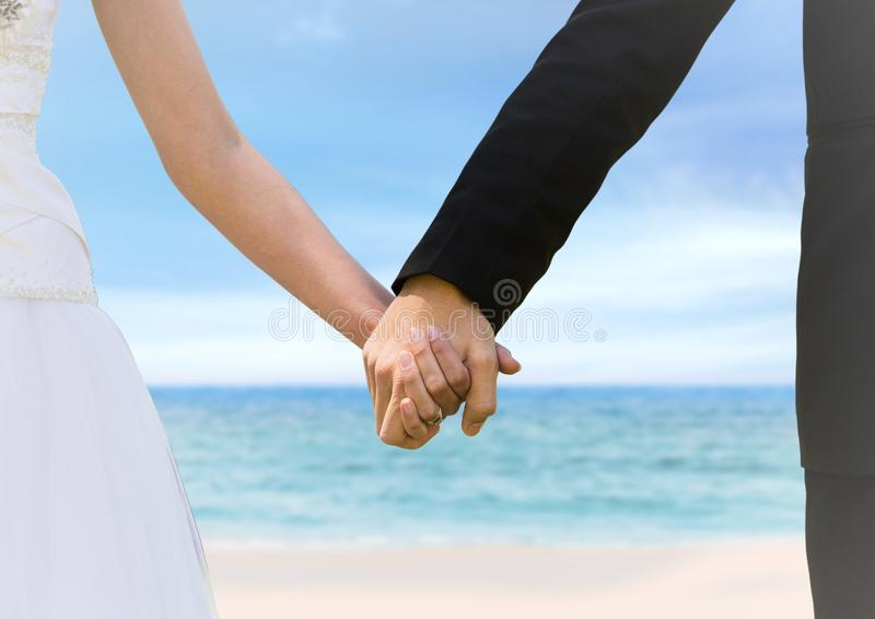 Bride and groom holding hands at blurry beach royalty free stock photos