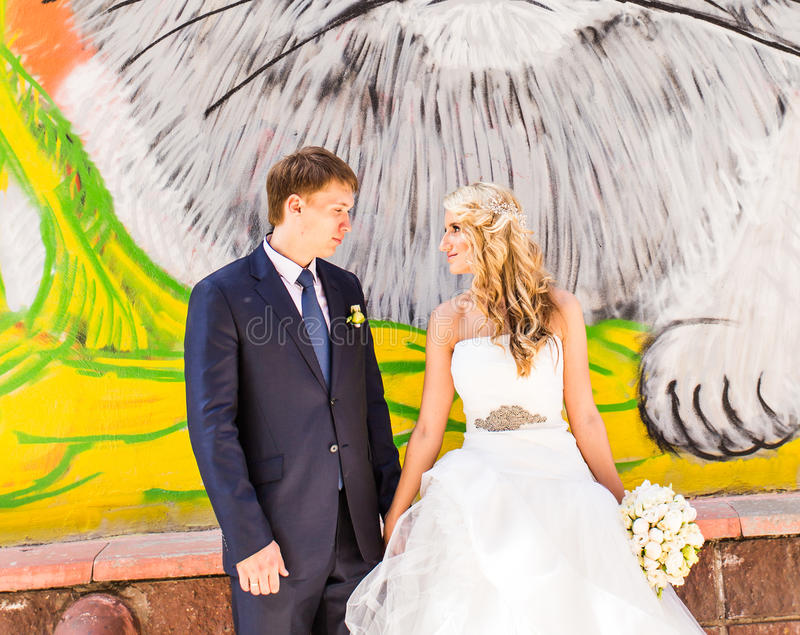 Bride and groom holding hands on graffiti wall background stock photos