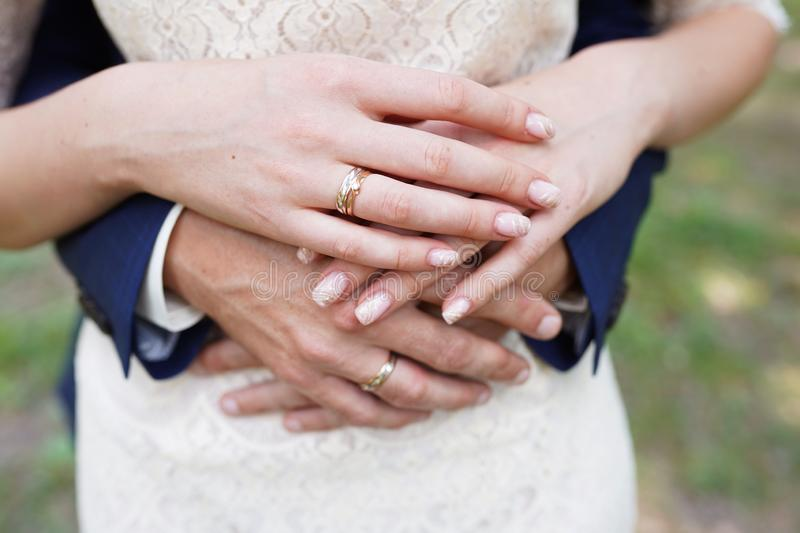 Bride and groom holding hands outdoors stock image