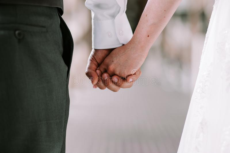 Bride and groom holding hands while walking stock photos