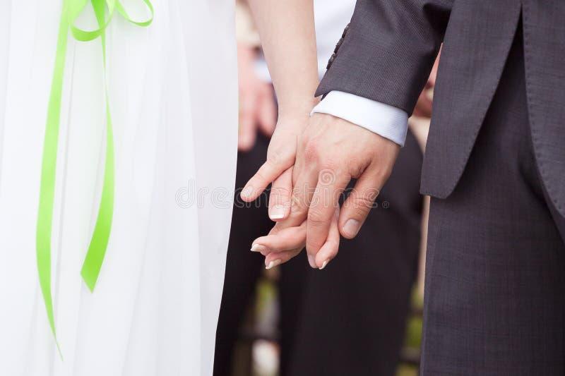 Bride and groom holding hands. Wedding ceremony - bride and groom holding hands royalty free stock photo