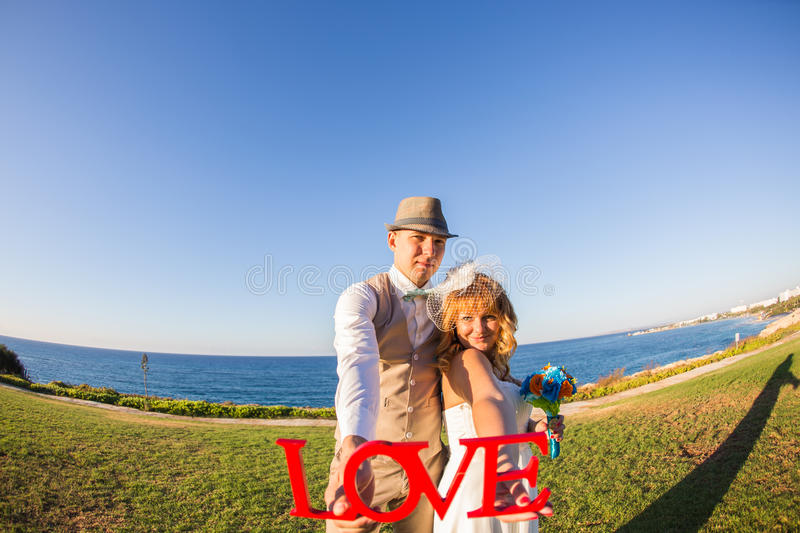 Bride and groom holding the letter word love royalty free stock photos