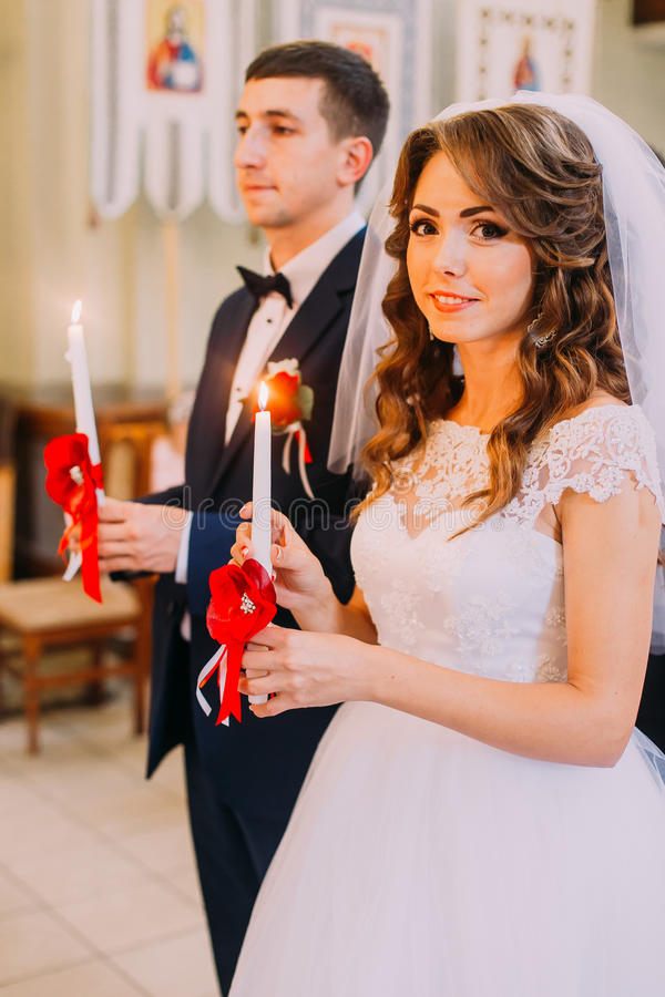Bride and groom holding lighted candles during the traditional wedding ceremony royalty free stock photography