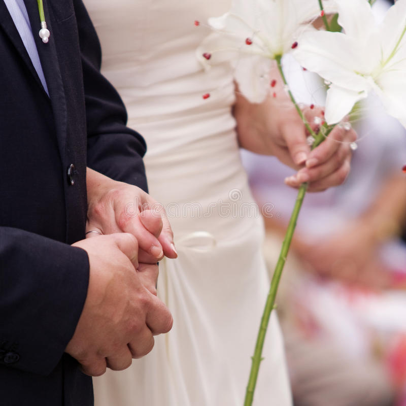 Bride and Groom holding their hands. Bride and groom holding each other's hands stock photo