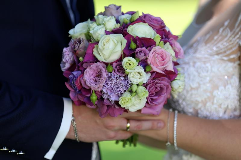 Bride and groom are holding a wedding bouquet.  stock image