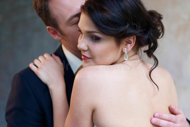 Bride and groom hugging in empty room royalty free stock image
