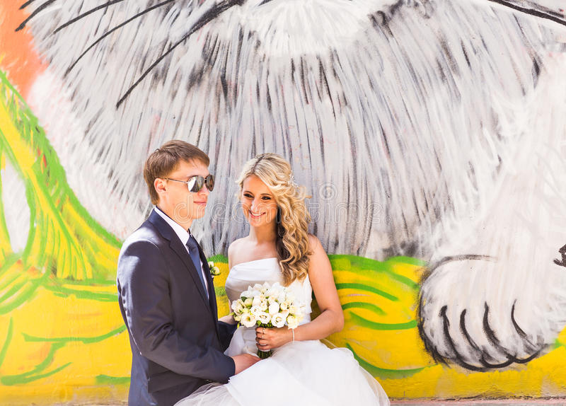 Bride and groom hugging on graffiti wall background.  stock photos