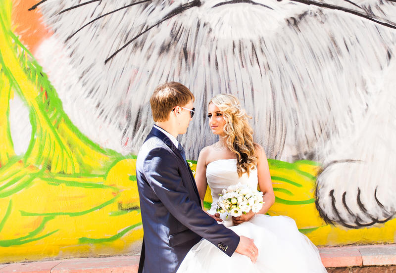 Bride and groom hugging on graffiti wall background.  royalty free stock image