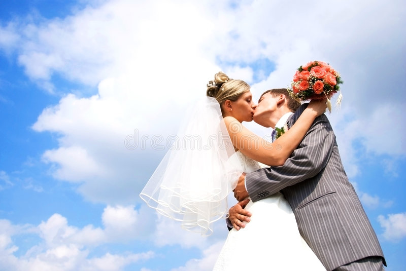 Bride and groom kissing against blue sky. Young bride and groom kissing against blue sky with clouds royalty free stock photos